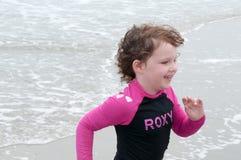 使用在海边的年轻逗人喜爱的小女孩遇到在一个沙滩的海浪在夏天阳光下 库存照片
