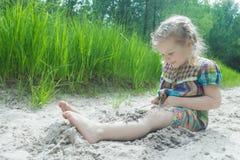 使用在海滩沙丘和埋葬的小女孩在白色沙子在夏天松林背景 免版税库存图片