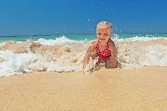 使用在海洋海浪的小女孩 免版税库存图片