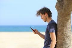 使用在海滩的一个可爱的人的侧视图一个巧妙的电话 库存图片