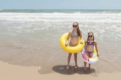 使用在海滩的两个女孩 免版税库存照片