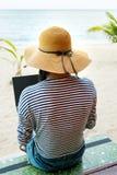 使用在海滩的女孩膝上型计算机 库存照片