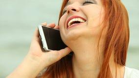 使用在海滩的妇女智能手机 库存图片
