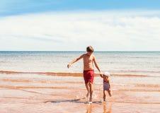 使用在海滩的小女孩和男孩 免版税库存图片