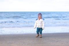 使用在海滩的小女孩在冬天 免版税图库摄影