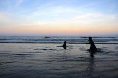 使用在海滩的小孩剪影在日落期间 免版税库存图片