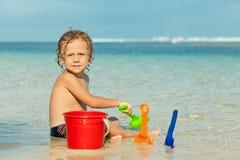 使用在海滩的小男孩在天时间 库存图片