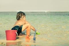 使用在海滩的小男孩在天时间 图库摄影