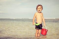使用在海滩的小男孩在天时间 免版税库存图片