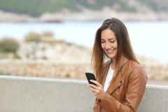 使用在海滩的愉快的妇女一个巧妙的电话与拷贝 免版税库存照片