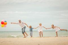 使用在海滩的愉快的家庭在天时间 免版税库存照片