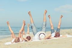 使用在海滩的愉快的家庭在天时间 免版税库存图片