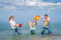 使用在海滩的愉快的家庭在天时间 免版税图库摄影