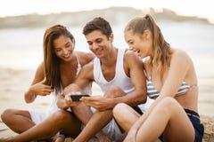 使用在海滩的朋友一个巧妙的电话 免版税库存图片