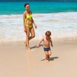 使用在海滩的母亲和两岁的男孩 库存图片