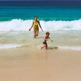 使用在海滩的母亲和两岁的男孩 免版税库存图片