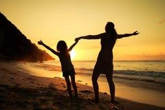 使用在海滩的母亲和女儿 库存照片