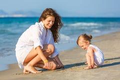 使用在海滩的母亲和女儿 图库摄影