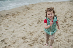 使用在海滨的沙子的小卷曲女孩 免版税图库摄影