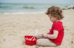 使用在海滨的沙子的小卷曲女孩 库存图片