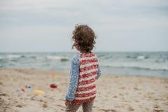 使用在海滨的沙子的小卷曲女孩 库存照片
