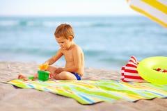 使用在海滩的沙子的逗人喜爱的孩子 免版税库存照片
