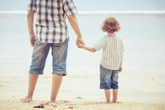 使用在海滩的父亲和儿子在天时间 免版税图库摄影