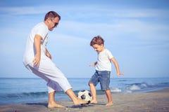 使用在海滩的父亲和儿子在天时间 免版税库存照片