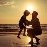 使用在海滩的父亲和儿子在日落时间 免版税库存图片