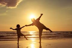 使用在海滩的父亲和儿子在日落时间 免版税图库摄影
