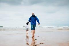 使用在海滩的父亲和女儿在一多云天 库存图片
