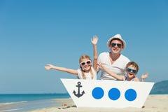 使用在海滩的父亲和孩子在天时间 图库摄影