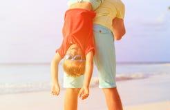 使用在海滩的父亲和愉快的矮小的儿子 库存照片