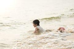 使用在海滩的逗人喜爱的亚裔男孩 免版税图库摄影