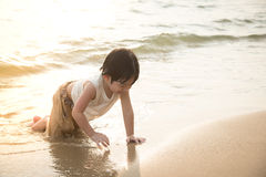 使用在海滩的逗人喜爱的亚裔男孩 免版税库存照片