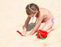 使用在海滩的逗人喜爱的微笑的小女孩 免版税库存照片