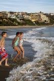 使用在海滩的青春期前的孩子跑入波浪 库存图片
