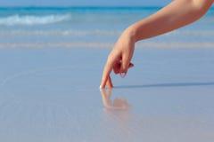 使用在海滩的水中的女性手 免版税库存图片