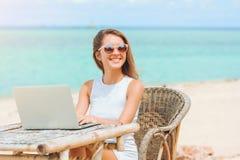 使用在海滩的年轻性感的妇女膝上型计算机 做自由职业者工作 图库摄影