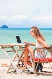 使用在海滩的年轻性感的妇女膝上型计算机 做自由职业者工作 免版税库存照片