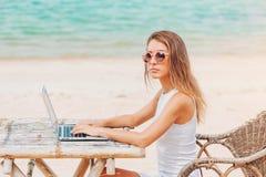 使用在海滩的年轻性感的妇女膝上型计算机 做自由职业者工作 库存图片