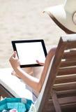 使用在海滩睡椅的妇女数字式片剂 库存照片