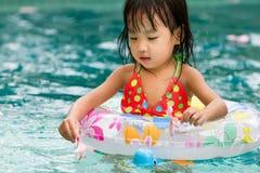 使用在游泳池的亚裔矮小的中国女孩 免版税库存图片