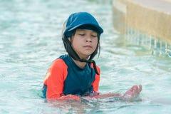 使用在游泳的训练水池的女孩,抹水在她的面孔外面 库存照片