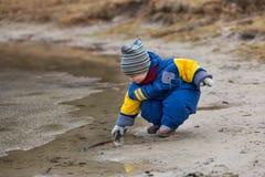 使用在湖岸的小男孩 免版税图库摄影