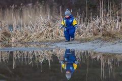 使用在湖岸的小男孩 图库摄影