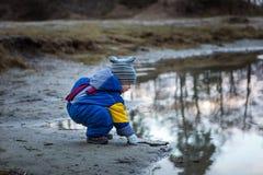 使用在湖岸的小男孩 免版税库存图片