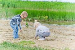 使用在湖岸的沙子的男孩和女孩  免版税库存照片