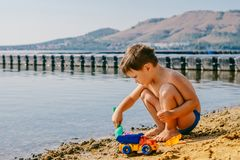 使用在湖的沙子的被晒黑的男孩 库存图片