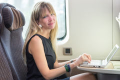 使用在火车的女商人计算机 免版税库存图片
